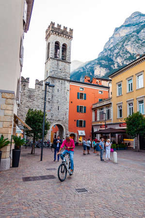 Riva del Garda, Lombardy, Italy - September 12, 2019: Scenic cityscape of Riva del Garda. Cozy city street full of tourists, plants and Italian architecture with high dolomite mountains on background 新聞圖片