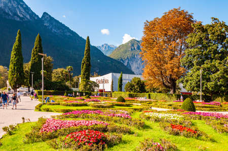 Riva del Garda, Lombardy, Italy - September 12, 2019: People walking by Garda lake promenade full of cozy alleys with growing and blooming plants and flowers Palavela congress center on background