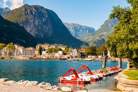 Riva del Garda, Italy - September 12, 2019: Beautiful Riva del Garda cityscape with vibrant red pedal boats parked in a row on the beach and city surrounded by high dolomite mountains on background