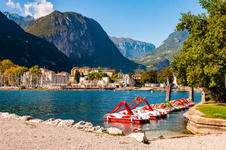 Riva del Garda, Italy - September 12, 2019: Beautiful Riva del Garda cityscape with vibrant red pedal boats parked in a row on the beach and city surrounded by high dolomite mountains on background 版權商用圖片 - 136499296