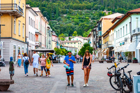 Riva del Garda, Lombardy, Italy - September 12, 2019: Scenic cityscape of Riva del Garda. Cozy city street full of tourists, plants and Italian architecture with high dolomite mountains on background 版權商用圖片 - 136499295