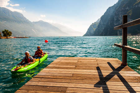 Riva del Garda, Lombardy, Italy - September 12, 2019: Two tourists arriving with kayak to the pier on the shore of Garda lake in Riva del Garda city in Italy, surrounded by high dolomite mountains 版權商用圖片 - 136499291