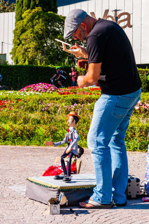 Riva del Garda, Lombardy, Italy - September 12, 2019: The artist puppeteer performing with his doll on promenade of Garda lake in Riva del Garda city