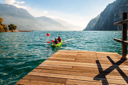 Riva del Garda, Lombardy, Italy - September 12, 2019: Two tourists arriving with kayak to the pier on the shore of Garda lake in Riva del Garda city in Italy, surrounded by high dolomite mountains 版權商用圖片 - 136499294