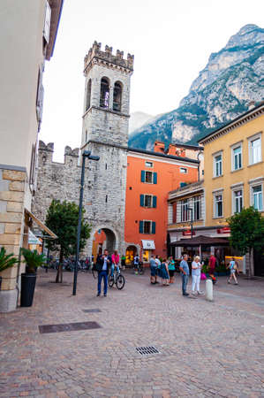 Riva del Garda, Lombardy, Italy - September 12, 2019: Scenic cityscape of Riva del Garda. Cozy city street full of tourists, plants and Italian architecture with high dolomite mountains on background 版權商用圖片 - 136499299