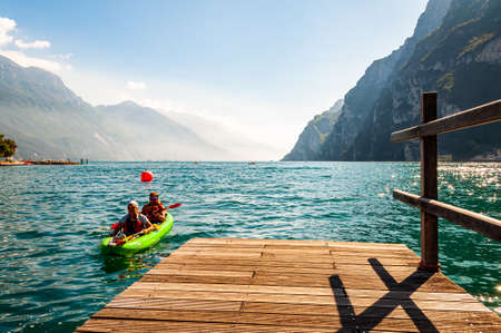 Riva del Garda, Lombardy, Italy - September 12, 2019: Two tourists arriving with kayak to the pier on the shore of Garda lake in Riva del Garda city in Italy, surrounded by high dolomite mountains 版權商用圖片 - 136499302