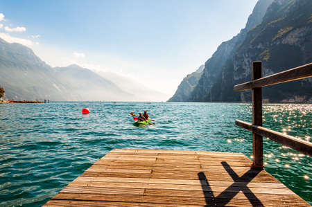 Riva del Garda, Lombardy, Italy - September 12, 2019: Two tourists arriving with kayak to the pier on the shore of Garda lake in Riva del Garda city in Italy, surrounded by high dolomite mountains 新聞圖片