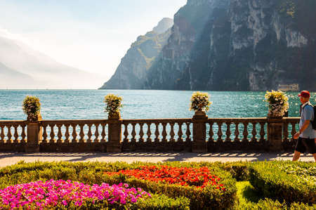 Riva del Garda, Lombardy, Italy - September 12, 2019: People walking by Garda lake promenade full of cozy alleys with growing and blooming plants, classic stone fence with flowerpots built on the edge 新聞圖片