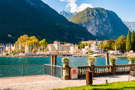 Riva del Garda, Lombardy, Italy - September 12, 2019: Beautiful Riva del Garda cityscape view with promenade and lake on foreground, city buildings surrounded by high dolomite mountains on background 新聞圖片