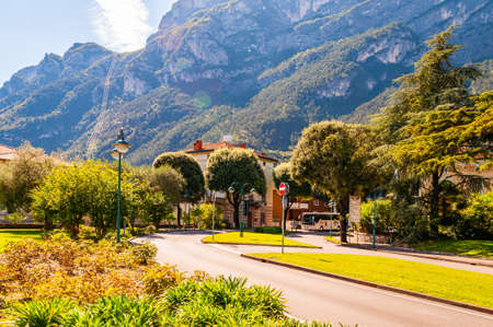 Riva del Garda, Lombardy, Italy - September 12, 2019: Scenic cityscape of Riva del Garda. Cozy city street full of plants and Italian architecture with high dolomite mountains on the background