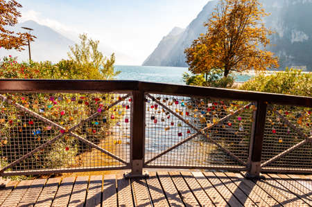 Riva del Garda, Lombardy, Italy - September 12, 2019: Love and marriage locks hanging on metal grid on wooden railings in Riva del Garda city with beautiful lake waterscape on the background 新聞圖片