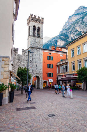 Riva del Garda, Lombardy, Italy - September 12, 2019: Scenic cityscape of Riva del Garda. Cozy city street full of tourists, plants and Italian architecture with high dolomite mountains on background 版權商用圖片 - 136650092