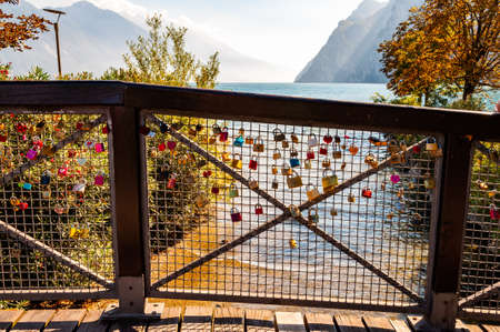 Riva del Garda, Lombardy, Italy - September 12, 2019: Love and marriage locks hanging on metal grid on wooden railings in Riva del Garda city with beautiful lake waterscape on the background 版權商用圖片 - 136650094