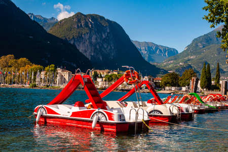 Riva del Garda, Italy - September 12, 2019: Beautiful Riva del Garda cityscape with vibrant red pedal boats parked in a row on the beach and city surrounded by high dolomite mountains on background 版權商用圖片 - 136650095