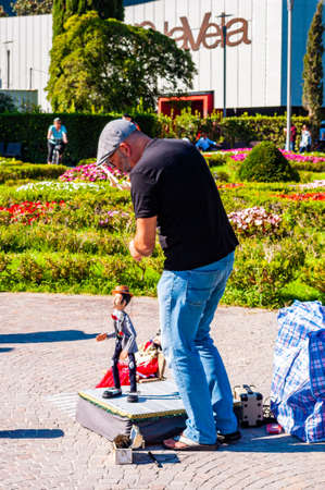 Riva del Garda, Lombardy, Italy - September 12, 2019: The artist puppeteer performing with his doll on promenade of Garda lake in Riva del Garda city