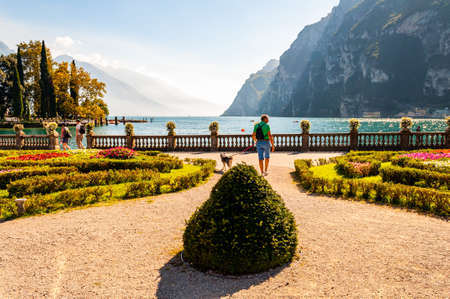 Riva del Garda, Lombardy, Italy - September 12, 2019: People walking by Garda lake promenade full of cozy alleys with growing and blooming plants, classic stone fence with flowerpots built on the edge 版權商用圖片 - 136650101