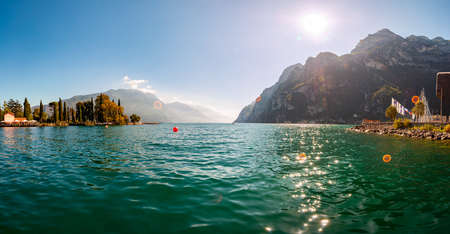 Riva del Garda, Lombardy, Italy - September 12, 2019: Panoramic view against bright sun rays above the rocks on beautiful Garda lake shore in Riva del Garda city surrounded by high dolomite mountains
