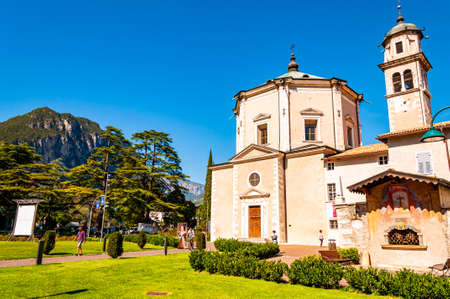 Riva del Garda, Lombardy, Italy - September 12, 2019: Chiesa di Santa Maria Inviolata church in Riva del Garda. City street, medieval Italian architecture with high dolomite mountains on background 版權商用圖片 - 136650102