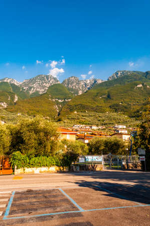 Riva del Garda, Lombardy, Italy - September 12, 2019: Scenic surroundings of Garda lake. Cozy villages, northern plants and Italian architecture with high green dolomite mountains on the background 新聞圖片