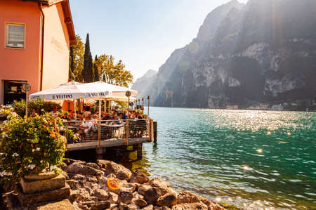 Riva del Garda, Lombardy, Italy - September 12, 2019: People sitting in cozy outdoor restaurant on the shore of Garda lake surrounded by high dolomite mountains with penetrating sun rays from above