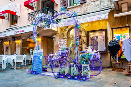 Sirmione, Lombardy, Italy - September 12, 2019: Violet purple vibrant heart shape arc, bicycle and bench decoration at the entrance to the lavender shop in the center of Sirmione city on Garda lake