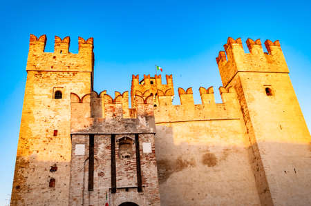Sirmione, Lombardy, Italy - September 12, 2019: Fortress walls of the Scaligero Castle or Castle of Sirmione illuminated by sunset sun on Garda lake
