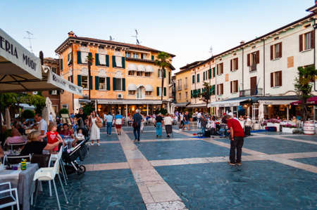 Sirmione, Lombardy, Italy - September 12, 2019: People walking by the streets of the famous Old Town of Sirmione city located on peninsula of Garda lake in Italy. Square full of restaurant