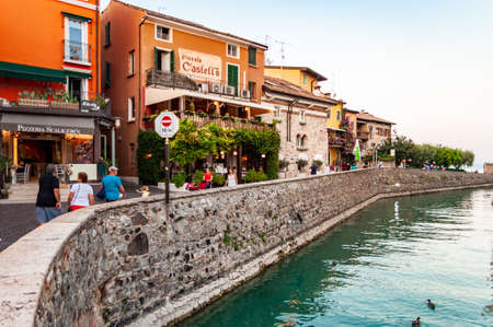 Sirmione, Lombardy, Italy - September 12, 2019: People walking around by the streets of the famous Old Town of Sirmione city located on peninsula of Garda lake in Italy. Canal around Scaligero castle