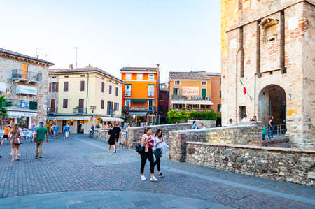 Sirmione, Lombardy, Italy - September 12, 2019: Fortress walls of the Scaligero Castle or Castle of Sirmione surrounded by water canals of the Garda lake. People walking around in medieval Old Town