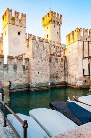 Sirmione, Lombardy, Italy - September 12, 2019: Motor boats parked in front of the fortress walls of the Scaligero Castle or Castle of Sirmione surrounded by water canals of the Garda lake