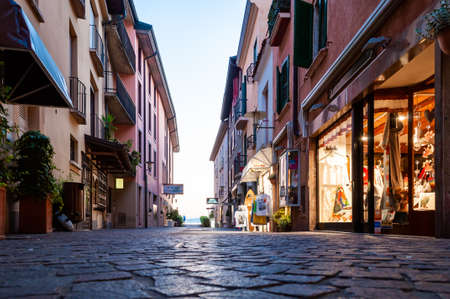 Sirmione, Lombardy, Italy - September 12, 2019: Late evening streets of the famous Old Town of Sirmione city located on peninsula of Garda lake in Italy. Polished paving stone streets full of shops