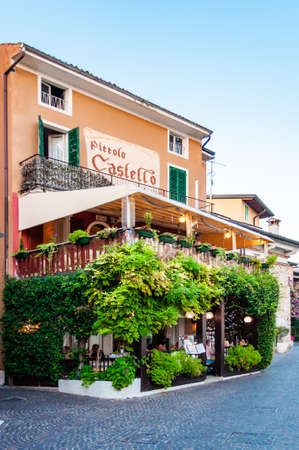 Sirmione, Lombardy, Italy - September 12, 2019: Cozy restaurant with green overgrown by grapes terrace located in the center of Sirmione Old Town in Lombardy, Italy 新聞圖片