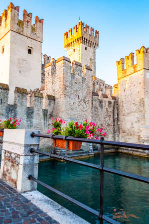 Sirmione, Lombardy, Italy - September 12, 2019: Fortress walls of the Scaligero Castle or Castle of Sirmione surrounded by water canals of the Garda lake.