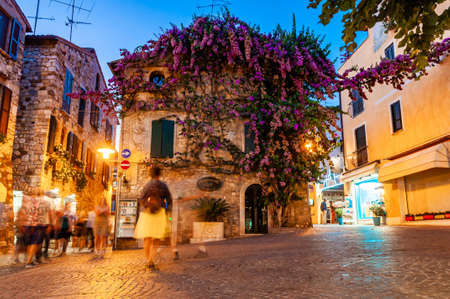 Sirmione, Lombardy, Italy - September 12, 2019: Cozy city streets in Sirmione. Vibrant violet purple flowers growing on facade of medieval building in Old Town. People walking by paving stone streets