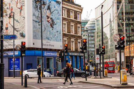 London, United Kingdom - September 14, 2017: People walking in downtown of London full of modern and traditional buildings, small and big businesses. Posters and banners hanging on facades.