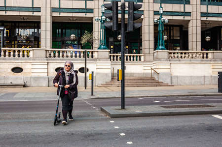 London, United Kingdom - September 14, 2017: Muslim woman with Kick scooter crossing the road in London downtown