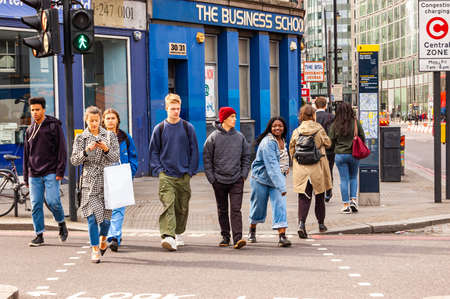 London, United Kingdom - September 14, 2017: People crossing the road in London. People walking in downtown of London full of modern and traditional buildings, small and big businesses