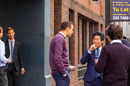 London, United Kingdom - September 14, 2017: Smoking break near the offices. People standing outdoors of their working places during the short break, talking to each other, smoking, drinking coffee.