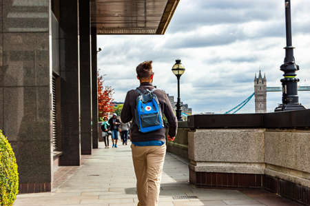London, United Kingdom - September 14, 2017: Man with blue bag on his back walking on riverside towards Tower Bridge in London