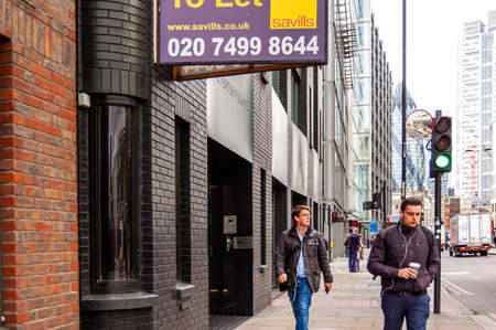 London, United Kingdom - September 14, 2017: People walking in downtown of London full of modern buildings, small and big businesses. Posters and banners hanging on facades. 新聞圖片