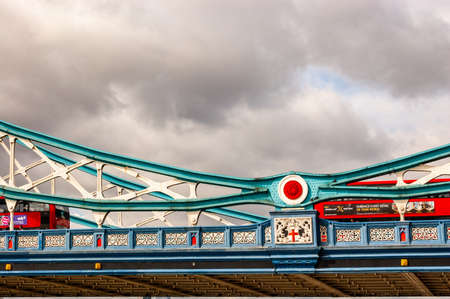London, United Kingdom - September 14, 2017: Classic red London buses crossing the vibrant and colorful fragment of the famous Tower Bridge in London. Colored metal constructions of the bridge. 新聞圖片