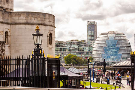 London, United Kingdom - September 14, 2017: Cityscape view of London with the Tower of London complex, people and tourists walking around and contemporary modern City Hall buildings on the background