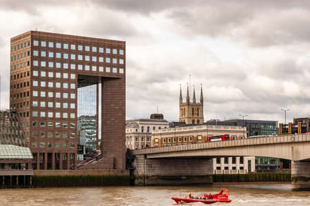 London, United Kingdom - September 14, 2017: View on red boat floating on Thames river, London bridge with moving transport on it and cityscape skyline on the background