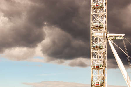 London, United Kingdom - September 14, 2017: Famous London Eye observation wheel located on promenade of Thames river. Heavy dark forecast cloud on the background.