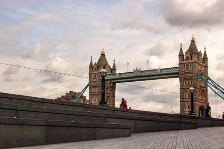 London, United Kingdom - September 14, 2017: Famous cityscape view of London. Thames river promenade with few people and amazing Tower bridge on the background 新聞圖片
