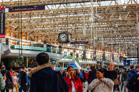 London, United Kingdom - September 14, 2017: Famous Waterloo station in London full of people, tourists, trains. Clock hanging from the metal glass roof