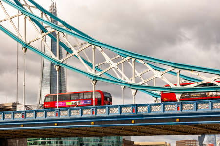 London, United Kingdom - September 14, 2017: Classic red London buses crossing the vibrant and colorful fragment of the famous Tower Bridge in London with the Shard skyscraper on the background