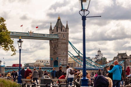 London, United Kingdom - September 14, 2017: Famous cityscape view of London. Thames river promenade full of people with amazing Tower bridge on the background