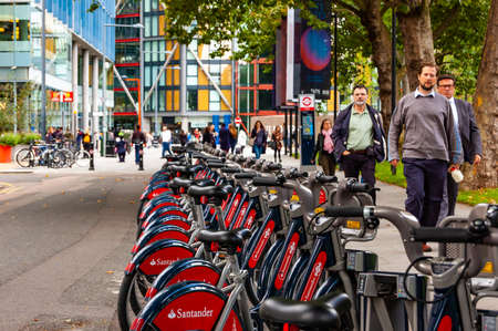 London, United Kingdom - September 14, 2017: Endless row of city bicycles in downtown of London. People walking no the street. 新聞圖片