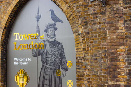 London, United Kingdom - September 14, 2017: The glass showcase of the Tower of London. Golden letters and signs with guard with raven sitting on his hat. Brick arc framing the showcase